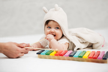 Baby girl playing xylophone toy on blanket at home