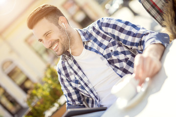 Young man sitting in cafe and enjoying
