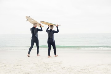 Senior couple in wetsuit carrying surfboard