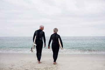 Rear view of senior couple in wetsuit holding a surfboard