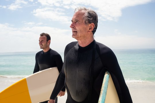 Father and son with surfboard walking on beach