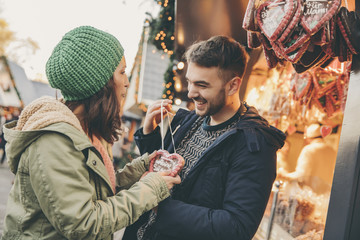 Woman receiving a gingerbread heart from her boyfriend on the Christmas Market