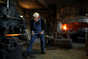Germany, Bavaria, Josefsthal, senior  blacksmith at work in historic blacksmith's shop