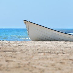 Old style white rowboat on a see beach