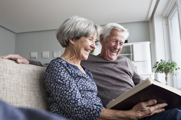 Laughing senior couple sitting on the couch at living room watching photo album