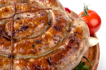 fried pork sausages on a wooden plate with cherry tomatoes and hot peppers