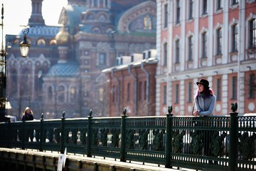 Stylish, young and beautiful girl with color hair poses on streets of St. Petersburg