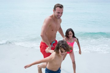 Happy children pulling father at beach