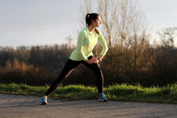 Young female runner doing exercise in evening sun