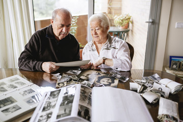 Senior couple watching their  old photographies and photo albums at home