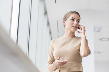 Woman in office talking on phone at the window