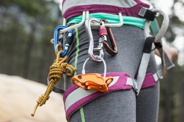 Midsection of woman with climbing equipment