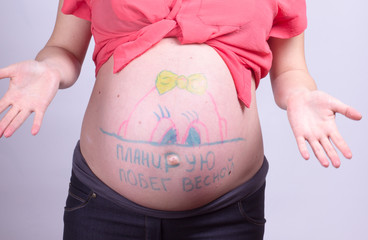 """Body art on belly of pregnant woman, the inscription in Russian, """"I plan to run in the spring"""""""
