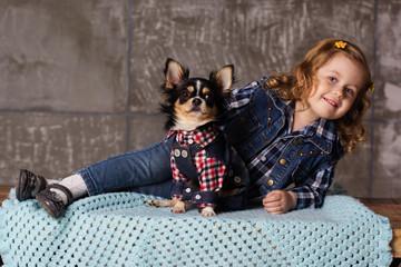 Little child girl is lying with chuhuahua dog