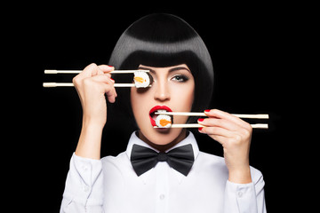 Beautiful woman eating sushi with chopsticks