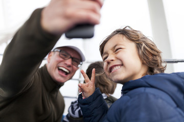 Laughing father taking a selfie with his son