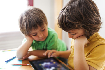 Two little brothers playing with digital tablet