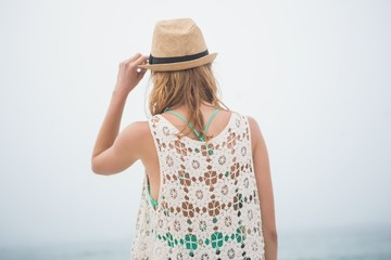 Cute blonde woman holding her straw hat