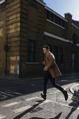 Young man in a hurry crossing urban street