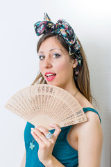 Woman in bathing suit holding a hand fan