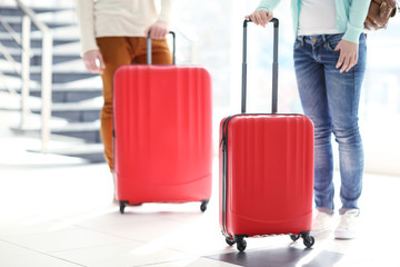 Couple waiting with large red suitcases, close up