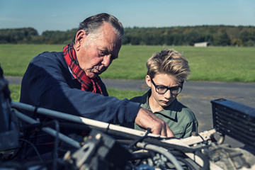 Germany, Dierdorf, Grandfather and grandson repairing biplane