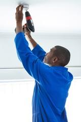 Handyman fixing the smoke detector with drill machine