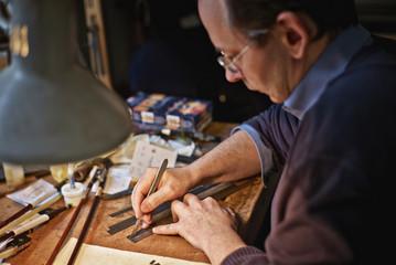 Violin maker in his workshop cutting veneer strips