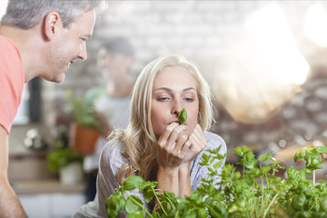 Smiling man looking at woman holding basil leaf