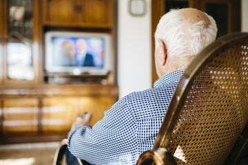 Back view of senior man sitting in his rocker watching television