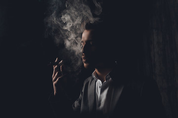 Attractive young man with cigar and smoke on black background