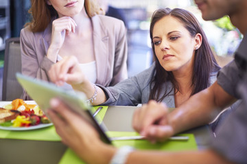 Businesswoman showing digital tablet to colleagues at dining table