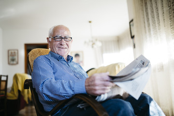 Portrait of smiling senior man with newspaper at home