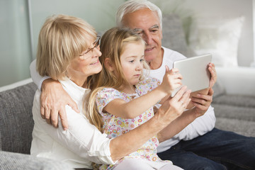 Senior couple and granddaughter looking at digital tablet at home