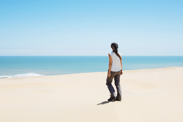 Namibia, Namib desert, Swakopmund, woman walking among the dunes of the desert to the sea