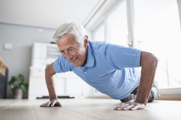 Portrait of senior man doing pushups at home