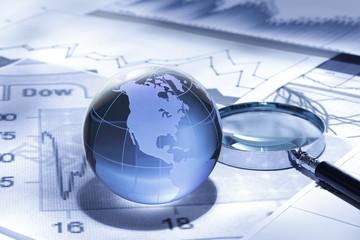 グローバルファイナンス/ガラス製の地球とファイナンシャルチャートとルーペ