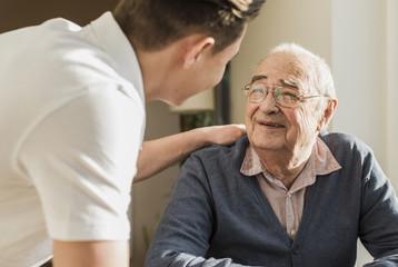 Portrait of smiling senior man face to face with his geriatric nurse