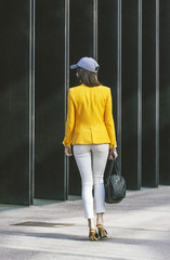 Spain,Catalunya, Barcelona, young modern woman with yellow jacket on the move, view from the back