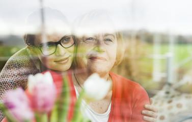Smiling young woman hugging senior woman behind windowpane
