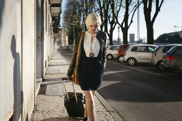 Italy, Verona, blond woman with luggage walking on a pavement