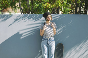 Portrait of serious looking young female skate boarder in front of blue wall