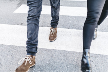Legs of man and woman walking on crosswalk