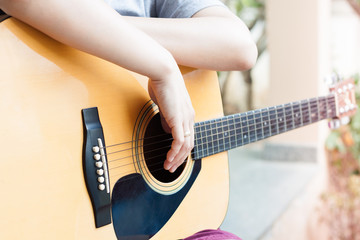 Woman's hands with acoustic guitar in relax post