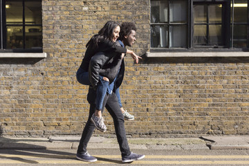 Young man carrying girlfriend piggyback at brick building