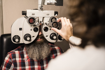 Bearded man at the optometrist making an eye test