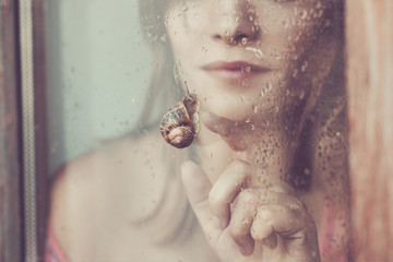 Woman watching snail creeping at outside of the windowpane, close-up
