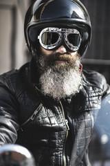 Portrait of bearded biker wearing black leather jacket, helmet and goggles
