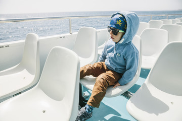 Spain, Mallorca, little boy with sunglasses and pirate bandana sitting on a tourist boat