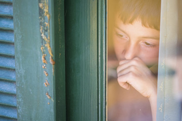 Portrait of boy looking through wondow